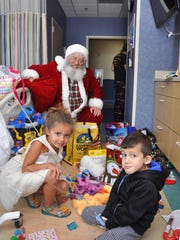 """Santa delivers a few more toys to Andrew and Kali Desjardins, who were celebrating Christmas in Golisano Children's Hospital. """"Santa"""" Dan Sutter has delivered holiday cheer to patients in the hospital for the last 5 years."""
