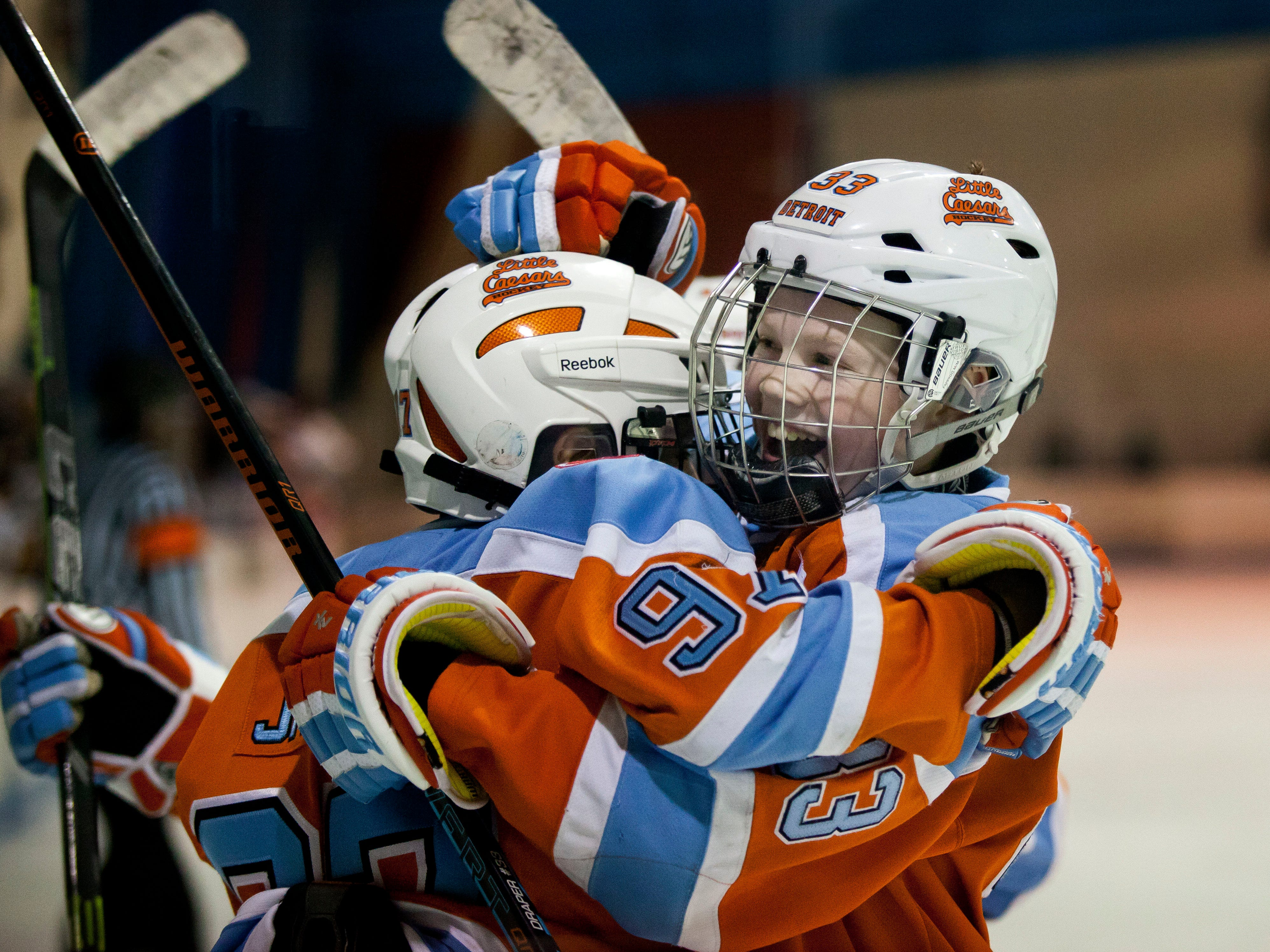 Detroit Little Caesars' Kienan Draper hugs Dominic James after he scored a goal during a Silver Stick Pee Wee AAA hockey game Friday, Jan. 9, 2015 at Glacier Pointe in Port Huron Township.