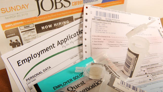 A forensic drug testing form with collection kit are seen along with an employment application form and a job opening advertisement section from a Sunday newspaper.