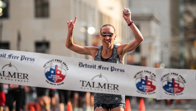 Lioudmila Kortchaguina crosses the finish line to win the women's race in the 39th annual Detroit Free Press/Talmer Bank Marathon in Detroit on Sunday, Oct. 16, 2016.