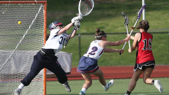 From right, Rye's Shannon Lavelle (18) gets a shot past Byram Hills goalie Charlie Rosiny (30) for a second half goal during girls lacrosse action at Byram Hills High School in Armonk May 10, 2018. Rye won the game 13-12.