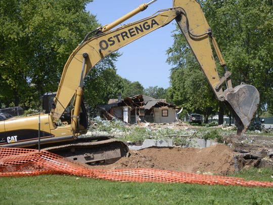 Crews are razing 16 houses along Brookwood Drive, most of them duplexes, to make way for a later townhouse project that is part of the Green Bay Packers' Titletown District.