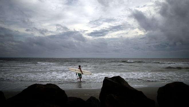 Kevin Taylor of Savannah, Ga., heads out to surf the waves on the north beach of Tybee Island as Hurricane Arthur makes its way up the East Coast on Thursday.