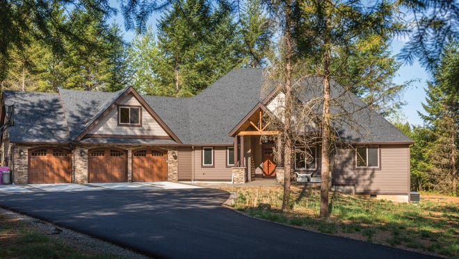 Modified from the plan to include a third garage bay and different siding materials, this graceful home creates a warm welcome.