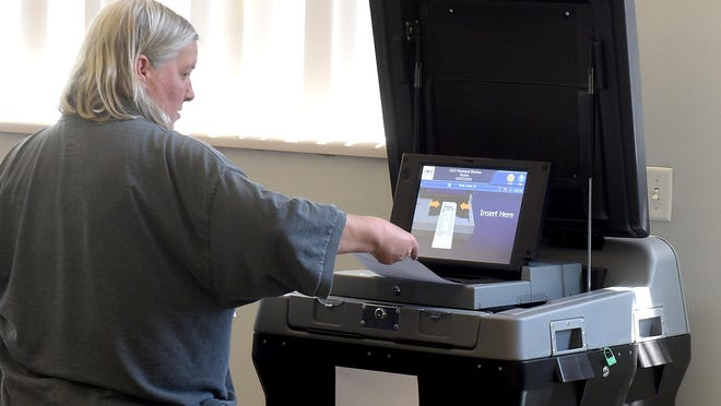 Paula Brower places her ballot in a counting machine after voting at Precinct 1B in the First Ward on Tuesday.