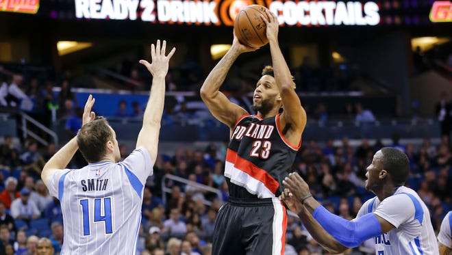 Portland Trail Blazers' Allen Crabbe (23) takes a shot between Orlando Magic's Jason Smith (14) and Victor Oladipo, right, during the first half of an NBA basketball game, Friday, Dec. 18, 2015, in Orlando, Fla.