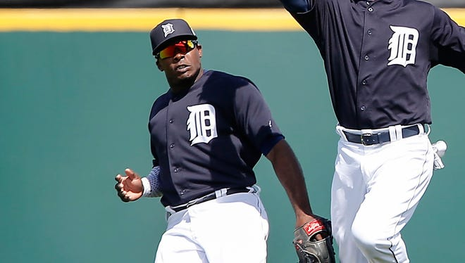 Mar 9, 2016; Lakeland, FL, USA; Detroit Tigers center fielder Anthony Gose (12) calls off right fielder Justin Upton (8) on a fly ball. Upton hurt his ankle in the ensuing collision and had to leave the game during the second inning of a spring training baseball game against the Washington Nationals at Joker Marchant Stadium.