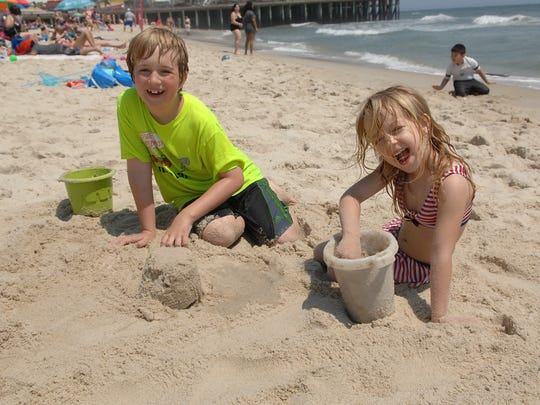 Ohio residents Ella Payton, age 5 (right), and Jackson Payton, age 9 (left), play in the sand on the Seaside Heights beach on Saturday, May 28, 2016.