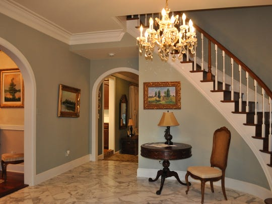 The grand foyer features a stunning staircase and entrance.