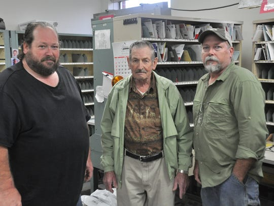 Casey (from left), Lowell and Eric Merrill gather inside the Mars Hill Post Office to celebrate Eric's Million Mile Award.