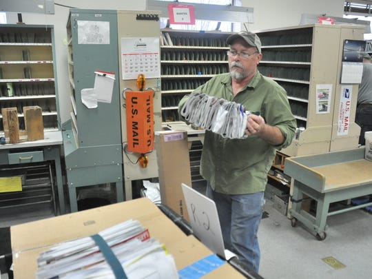 Eric Merrill gathers letters for his 74-mile route covering U.S. 19, which typically takes him about five hours to complete.
