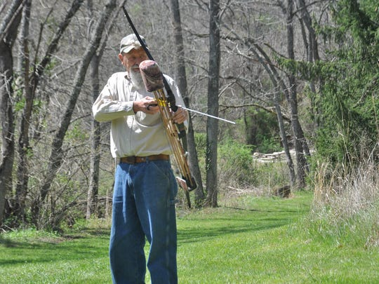 Mike Treadway takes aim in his yard with one of his longbows.