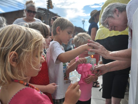 Mary Filiss helps a group of young children light candles for the vigil to victims of racist violence.