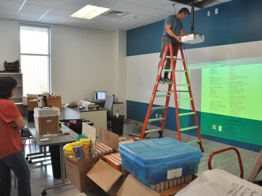 Paul Barilovits  installs an overhead projector with Shawn Randall.