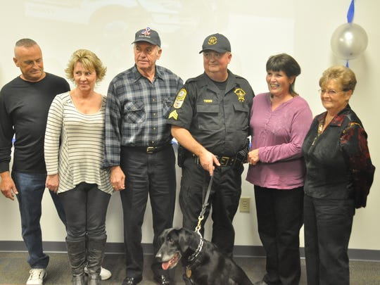 Sergeant Jeff Tweed hangs on to Tyler during his retirement party for a family picture with (from left) his brother Rick, sister-in-law Joyce, father Dennis, wife Elaine and mother Marie.