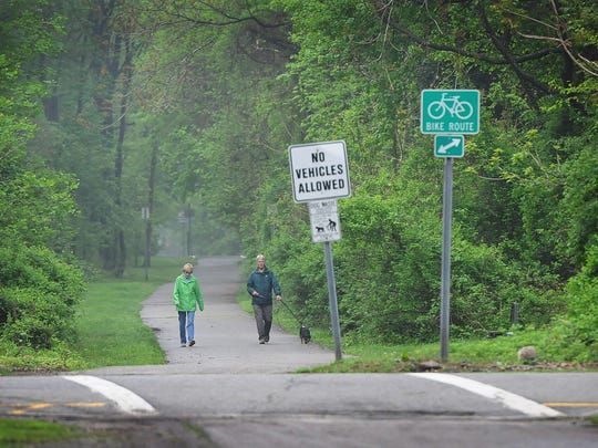 A couple takes a walk with a dog  on Ramsey Bikeway, an asphalt hiking and biking path several miles long, runs along the route of the old NJRT trolley line (1911 to 1928). It's one of 50 NJ rail trails created from the old right-of-ways of disused railroad lines.