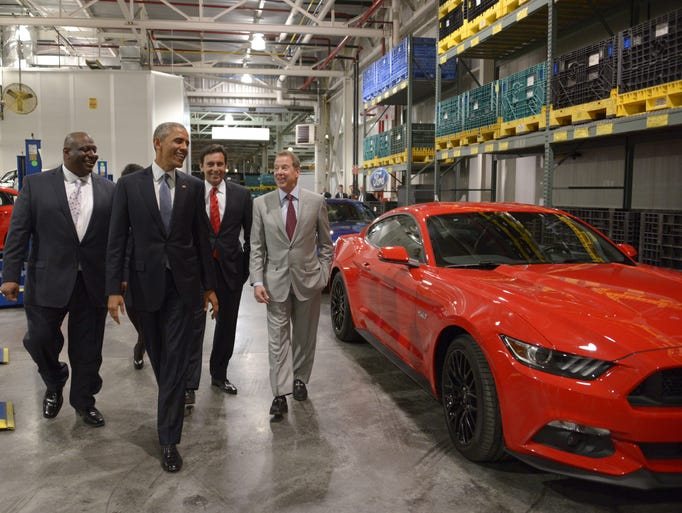 President Barack Obama passes a Ford Mustang as he