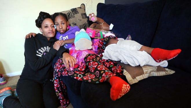 Shanita Miller sits with her daughter Sinai Miller, 9, as she heals from being shot in the leg while she and her two young sisters were preparing to sell Girl Scout cookies in their neighborhood.