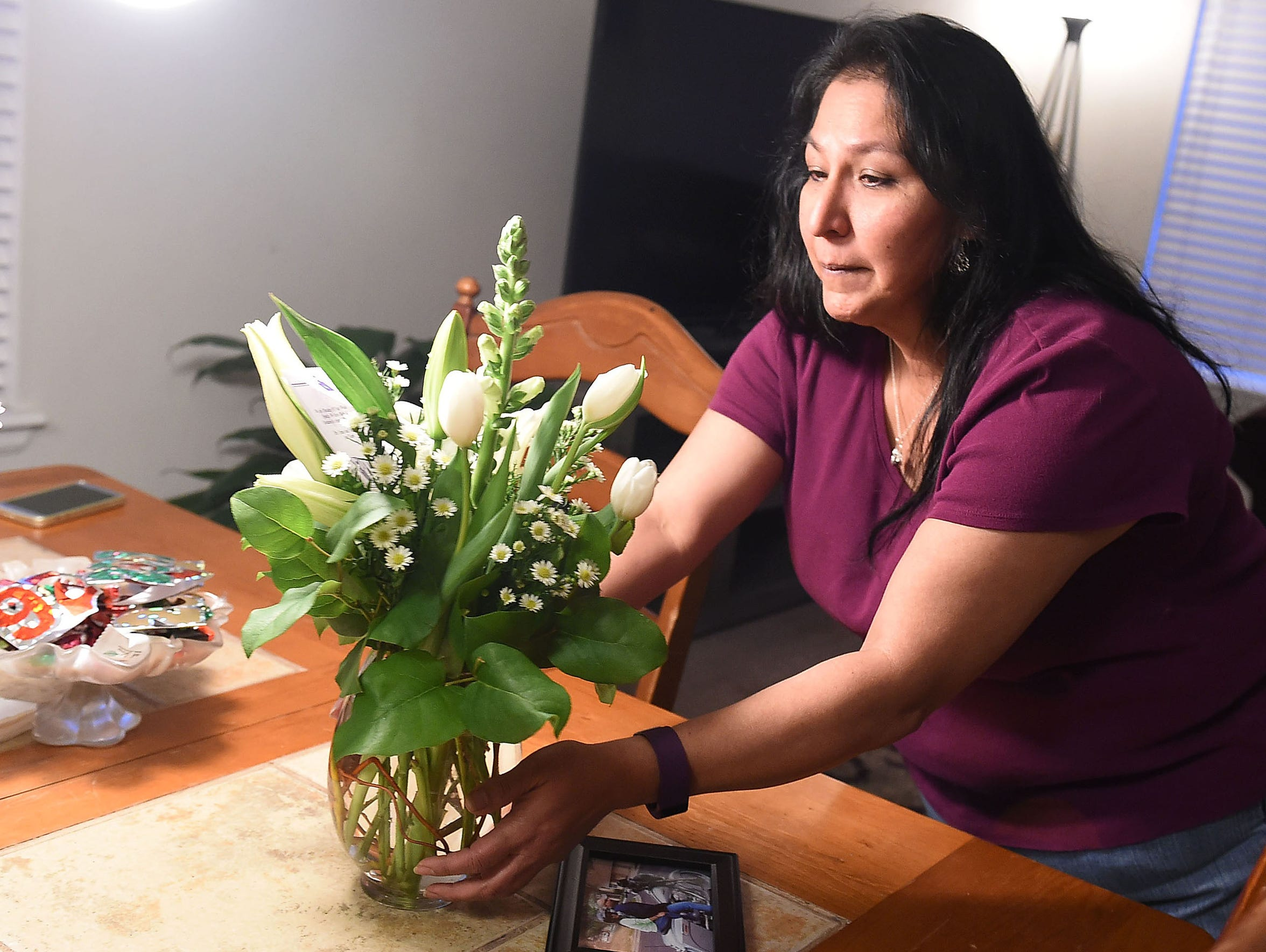 Gigi Godinez places a flower arrangement from her daughter