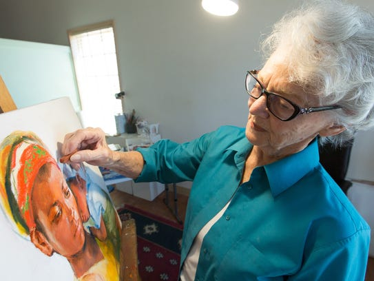 Artist Carolyn Bunch works on a painting on at her