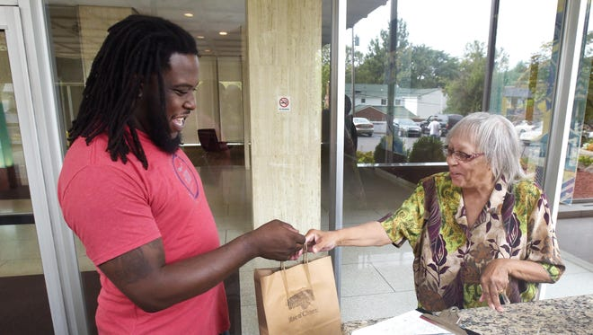 Ryan Fields delivers an order from the restaurant Mac n' Cheez on Warren to Janet Maxwell at her Jefferson Avenue apartment last month.