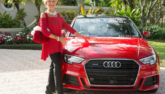 Woman's Club of Stuart Past President Pam Alverson admires a cherry-red Audi in front of one of the homes on last December's Holiday Home Tour.