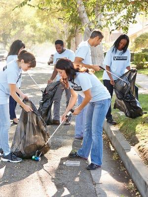 Team Of Volunteers Picking Up Litter In Street