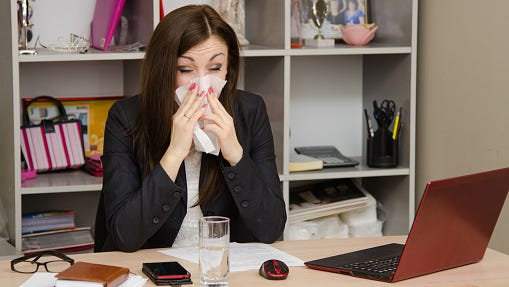 Girl wiping nose with a tissue in the office