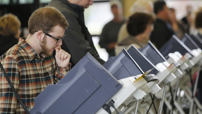 Zachary Palmer pauses while examining the ballot as he votes in the 2014 election Tuesday, November 4, 2014. A push to eliminate straight party-line voting on Indiana election ballots has been sidelined in the state Senate.