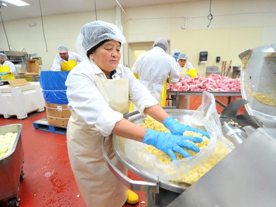 Worker Mai Moua, 55, of Wausau, collects grounded garlic on Oct. 18, 2015, at Mekong Fresh Meat in Mosinee.