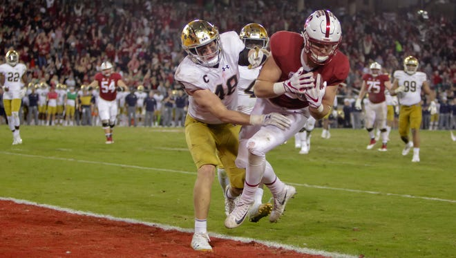 Nov 25, 2017; Stanford, CA, USA; Stanford Cardinal tight end Dalton Schultz (9) catches a touchdown pass over Notre Dame Fighting Irish linebacker Greer Martini (48) during the fourth quarter at Stanford Stadium. Mandatory Credit: Sergio Estrada-USA TODAY Sports