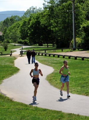 Runners enjoy the greenway at Carrier Park.   The Asheville Riverfront office will hold a Grilling on Greenways meeting June 27.