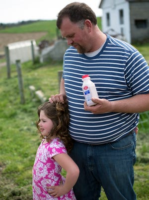 Brian Aukema stands with his daughter Annaleen on the Aukema Dairy Farm. The farm will participate in the 2016 Farm Trail Weekend where they will host a petting zoo, milks tastings, and farm tours.