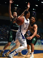 Weber State's Joel Bolomboy (21) is guarded by North Dakota's Drick Bernstine, left, and Quinton Hooker at the Reno Events Center in the Big Sky tournament last year. .