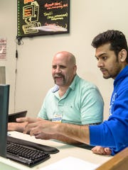 Student worker Jeremy Wells, 46, left, receives assistance from Avee Patel, right, during his shift at the computer help desk in the library at Jefferson County Technical College. April 6, 2017