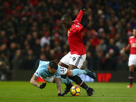 Manchester City's Nicolas Otamendi, left, fights for the ball with Manchester United's Romelu Lukaku during the English Premier League soccer match between Manchester United and Manchester City at Old Trafford Stadium in Manchester, England, Sunday, Dec. 10, 2017. (AP Photo/Dave Thompson)