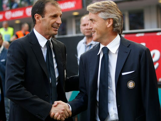 Inter Milan coach Roberto Mancini, right, shakes hand with Juventus coach Massimiliano Allegri prior to the start of a Serie A soccer match between Inter Milan and Juventus, at the San Siro stadium in Milan, Italy, Saturday, May 16, 2015. (AP Photo/Luca Bruno)