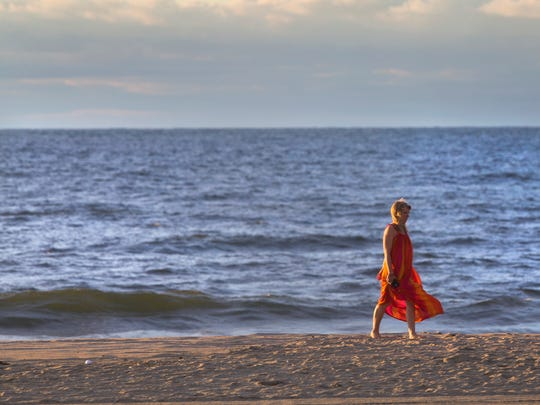 A woman walks along the Asbury Park beach in the early