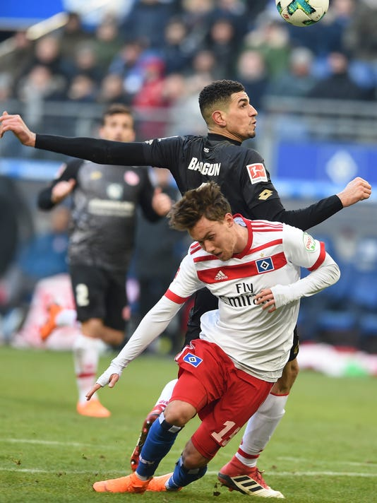 Mainz'  Leon Aderemi Balogun, behind, and Hamburg's Luca Waldschmidt, front, challenge for the ball  during the German Bundesliga soccer match between Hamburger SV and FSV Mainz 05, in Hamburg, Germany, Saturday, March 3, 2018. (Carmen Jaspersen/dpa via AP)