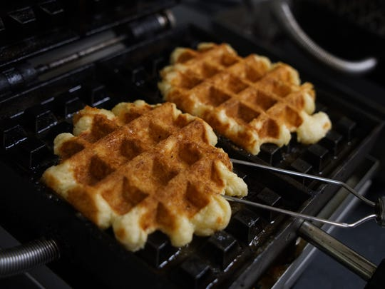 Cooked Belgian waffles get removed from an iron at the Perfect Blend in Newark.