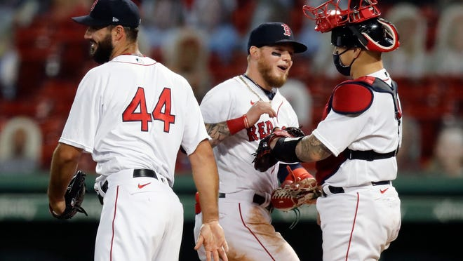 Boston Red Sox's Alex Verdugo, center, celebrates with Brandon Workman (44) and Christian Vazquez after the Red Sox defeated the Toronto Blue Jays during a baseball game, Friday, Aug. 7, 2020, in Boston.