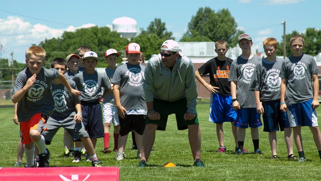 CSU football coach Mike Bobo, center, instructs kids at the Rams' satellite camp in Yuma.