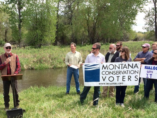 Gov. Steve Bullock, second from left, watches as he receives the endorsement of Dave Tyler of the Montana Conservation Voters in May.
