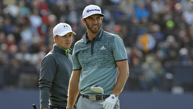 United States' Dustin Johnson, left, follows his drive from the 18th tee as United States' Jordan Spieth walks onto the tee during the second round of the British Open Golf Championship at the Old Course, St. Andrews, Scotland, Saturday, July 18, 2015.