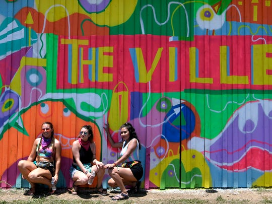 """Taylor Clark of Clarksville, Cynthia Cruz of Clarksville and Gaby Lee of Texas pose with """"The Ville"""" mural June 7, 2018, at the Bonnaroo Music & Arts Festival in Manchester, Tenn."""