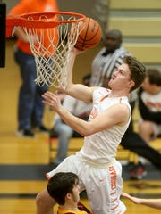Central Kitsap's Austin McMinds drives for a basket over Capital's Dawson Landers during Friday's South Sound Conference 3A game. Central Kitsap won 42-38.