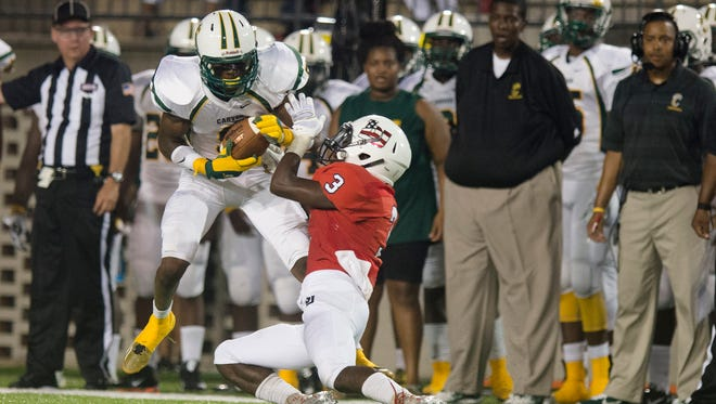 Carver wide receiver Xavier Lane (9) pushes Bob Jones defensive back Milkyle Stewart down during the AHSAA Championship Challenge game Saturday, Aug. 22, 2015, at Cramton Bowl in Montgomery, Ala.
