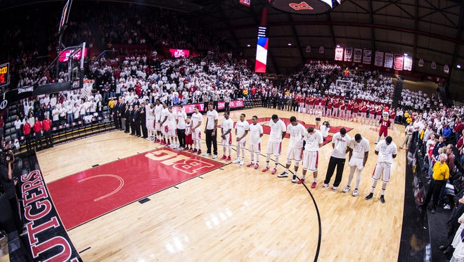 Rutgers players stand for the national anthem.