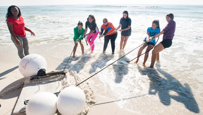Teasia Toston,17, looks on as Alexis Patel, 16, left to right, Charlene Mauro (director of the Navarre Beach Marine Science Station), Heather Barrineau (assistant director), Lauren Myers, 16, Erin Figueroa, 16, and Katie Collins, 17,  pull an anchor platform into the gulf at Navarre Beach on Wednesday, December 7, 2016.  The platform will be submerged to position an underwater camera and monitoring equipment in order to study and observe the reef offshore.