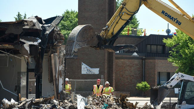 Crews concentrate on a portion of the structure while demolishing former Holiday station Thursday, July 6, on the East Side of St. Cloud.